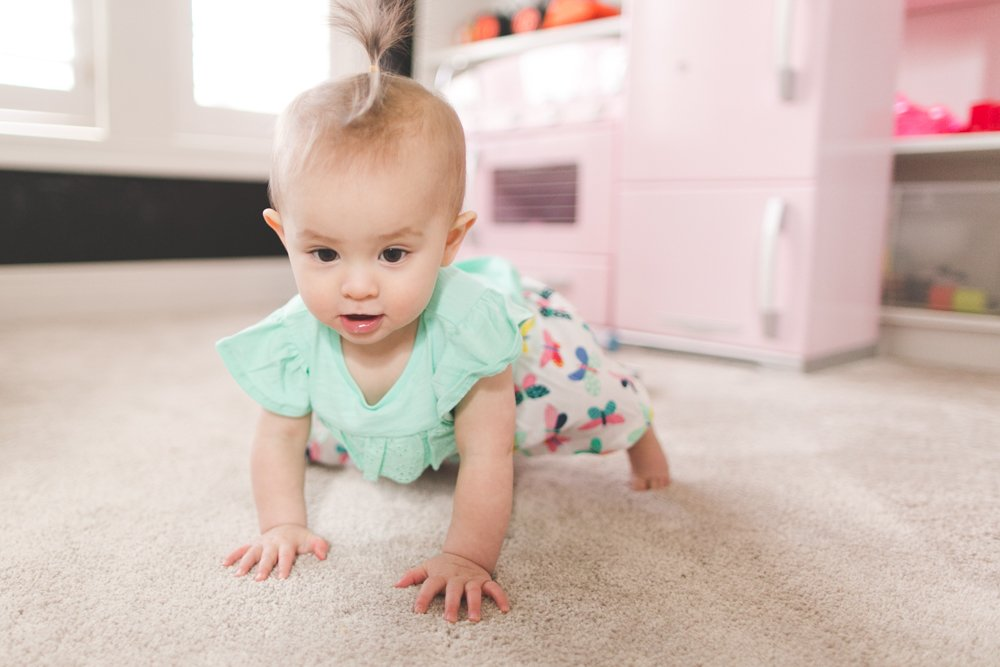 nine month baby milestones - baby with lemon outfit from carters