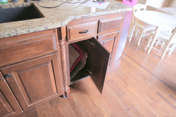 Learn how to make a DIY trash can pull out cabinet to hide ugly trash cans and recycle bins!