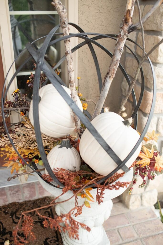 faux pumpkin and fall decor in metal orb sphere gardening